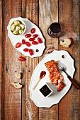 Antipastiplatten mit Lachs, Tomaten, Artischocken, Brot und Rotwein