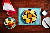 Orangen (halbiert, Schnitze) und frischer Obstsalat