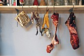 Smoked meat, fish and poultry on hooks