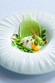Poached eggs with young peas and beetroot leaves on mushy peas