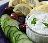 A bowl of tzatziki with cucumber, olives and lemon (close-up)