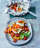 Feta cheese with cherry tomatoes in aluminium foil with balsamic vegetables