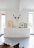 Massgefertigte weiße Ablage mit Bilderrahmen und Tiertrophäe an Wand in reduziertem Landhausstil mit Dielenboden