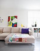 Patchworkdecke und violettes Kissen auf heller Sofakombination, modernes Bild auf Ablage an Wand lehnend