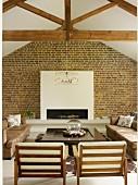 Sessel mit weissen Polstern auf Holzgestell und Sofas um Bodentisch vor Kamin in weisser Vorsatzschale an Ziegelwand