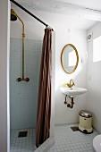 Abgetrennter Duschbereich mit braunem Vorhang, seitlich Waschbereich, ovaler Spiegel mit Goldrahmen an Wand