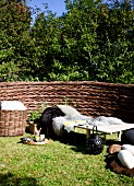 Idyllisches Ruheplätzchen im Garten, Sonnenliege mit Tierfellen, daneben Tablett auf Rasen