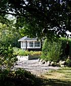 Hochbeet mit Holzeinfassung auf Kiesboden im Garten, im Hintergrund teilweise sichtbarer Pavillon aus dunklem Holz