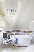 Ablage mit Mosaik aus bunten Scherben und Fliesenbordüre hinter freistehender Badewanne und einem Antikstuhl; Kronleuchter mit Schirm im Vordergrund