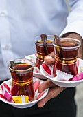 Three glasses of Turkish tea being served