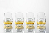Four glasses of whiskey with ice cubes