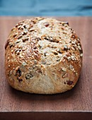 A loaf of country bread with seeds on a wooden board