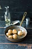 Mini potato dumplings being rolled in breadcrumbs