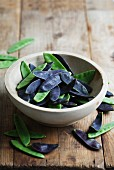 A bowl of green and purple mange tout