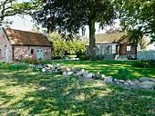 Steinbrocken im Garten, im Hintergrund Gartenhaus und Landhaus mit Ziegelfassade