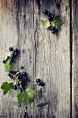 Blackcurrants with leaves on a wooden surface