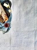 Brot, Baguette und Rotwein auf weisser Picknickdecke
