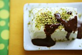 An ice cream cake with pistachios and chocolate and coffee sauce