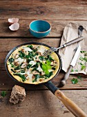 A spinach and mushroom omelette in the pan