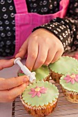 A little girl decorating a cupcake with sugar flowers
