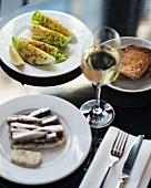 Verschiedene Tapas (Sardinen, Salat) mit Wein und Brot