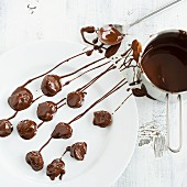 Chocolate-covered plums being made
