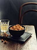 A bowl of spiced popcorn next to a glass of white wine