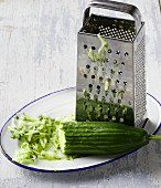 A grater and grated cucumber