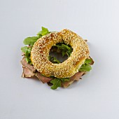 A sesame seed bagel with roast beef and rocket