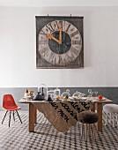 Raum im Stilmix mit Keramikfliesen, gedecktem Tisch mit Glaswaren, Eames Chair und alter Kirchturmuhr an der Wand