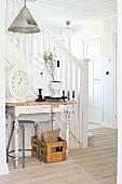 Wandtisch mit abblätternder Farbe vor Treppenlauf mit weißem Holzgeländer in Diele