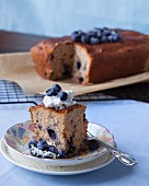 A coffee cake with blueberries and whipped cream