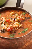 Barley soup with vegetables in a copper pot (close up)