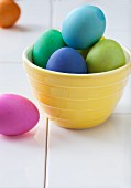Colourful Easter eggs in a yellow bowl
