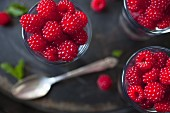 Fresh raspberries in shot glasses (seen from above)