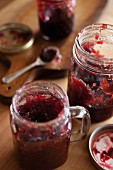 Jars of blueberry and strawberry jam on a wooden table