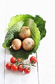 A savoy cabbage, onions and cherry tomatoes