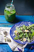A mixed leaf salad with young peas and quail's eggs served with a herb smoothie on a blue wooden table