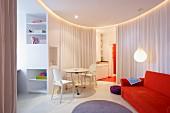 Orangerotes Sofa und weiße Ghost Stühle mit Tisch in kreisförmigem Wohnbereich, Vorhang als Raumteiler in modernem Ambiente