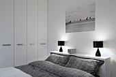 Doppelbett mit grauer, gemusterter Bettwäsche, an Kopfende Ablage mit schwarzen Tischleuchten in modernem Schlafzimmer mit weißem Einbauschrank