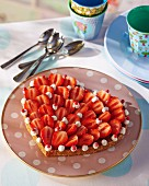 A heart-shaped strawberry tart with cream piping