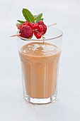A glass of coconut and macadamia nut smoothie with strawberries garnished with a fruit and mint skewer
