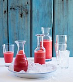 Watermelon lemonade in bottles and a glass