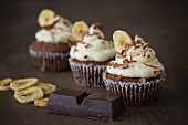 Chocolate cupcakes with a banana topping with cooking chocolate and banana chips next to it