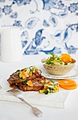 Pork chops in a spicy clementine and avocado salsa with sweetcorn