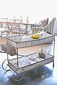 Filigraner Teewagen mit Gitterstäben um Ablagen, darauf Geschirr, im Hintergrund Essplatz mit Rattanstühlen und Sessel in hellem Licht