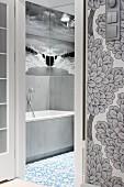 Blick durch offene Tür ins Badezimmer auf eine Übereck gespiegelte Fototapete mit Schwarz-Weiß-Abbildung von Meer und Himmel