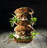 A stack of lamb burgers with rocket