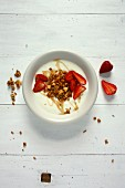 A bowl of granola (crunchy muesli) with yoghurt and strawberries