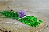 Frischer Schnittlauch mit Blüte auf Holzbrett